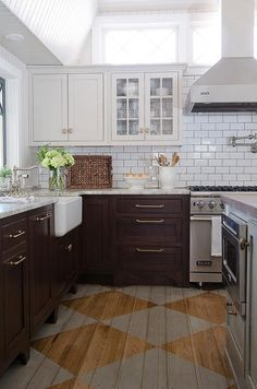 Amazing kitchen features light grey upper cabinets and dark brown lower cabinets paired with gray granite countertops and a white subway tiled backsplash with dark grout.