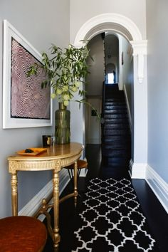 Before & After: a Victorian terrace becomes a beautiful contemporary home: A gold hall table from London's The Grosvenor Hotel is mismatched to a black-and-white rug and Warlimpirrnga Tjapaltjarri's Tingari painting in a hallway that, once stark white (as per 'before' image, slide 2), was recoloured in Resene's 'Half Stack'.