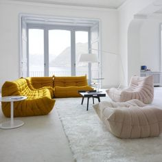 Ligne Roset couches + seats | Bright mustard yellow + blush pink surrounded by white walls + floor with a lakeside view