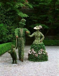 a topiary couple walking their dog along the garden path.
