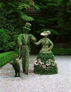 a topiary couple walking their dog along the garden path.