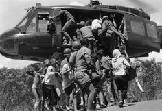 Lightly-wounded civilians and troops attempt to push their way aboard a South Vietnamese evacuation helicopter hovering over a stretch of Highway 13 near An Loc in Vietnam on June 25, 1972.