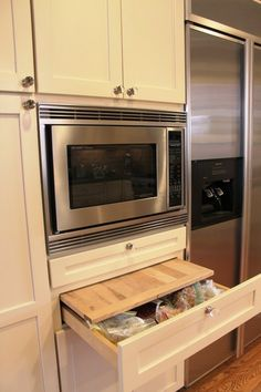 A cutting board and shallow drawer installed at counter height under the microwave providing extra counter space and functional storage. By Laura Rodman Designs.