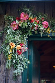 Set the scene for guests with a festive garland made of greens, florals, and berries! #holiday
