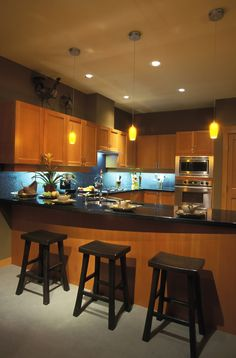 Modern look kitchen flush with warm natural wood tones, contrasting with glossy black countertops and blue-lit tile backsplash.