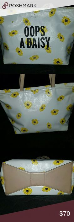 """Kate Spade Oops a Daisy shoulder bag Adorable Oops A Daisy tote bag loved through the season. Allover daisy print with """"Oops A Daisy"""" across the front. Top zip closure. Dual carrying straps. Signature logo hardware detail in front. Flat base with signature bow paneling to provide upright structure. Custom woven Quick and Curious interior lining. Interior features a back-wall zip pocket and two front-wall slip pockets. Small red stain on front near the bottom that was probably snowcone syrup…"""