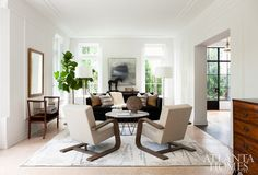 The living room was painted crisp white to emphasize the original architecture. Striking a 21st-century note are a pair of bentwood upholstered chairs from Bungalow Classic and a metal cocktail table from Holland & Company. A rug from Moattar softens the terrazzo floor.
