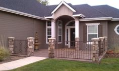 metal fence with stone pillars surrounding the front patio