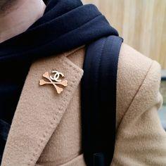 Chanel vintage crossbones pin brooch in gold hardware and enamel. London street style detail shot.