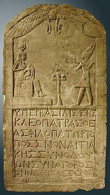 Cléopatre VII représentée vêtue en pharaon sur une stèle inscrite en grec et dédiée par un Grec adepte du culte d'Isis, 51 av. J.-C., musée du Louvre