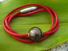 Tiki carved pearl on an unbreackable red sankeskin cord. Safety clasp.