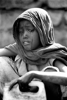 A young Somali girl cries as she waits in line for a bucket of water from a dry well. (image by Gary Ramage)