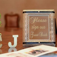 """Please sign our guest book"" gold frame placed next to guest book for guests to sign 