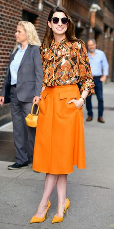 Anne Hathaway (and her stylist Law Roach) showed us the power of mixing bright hues by tucking in an Anna Sui top into an orange Rochas skirt and styling the look with yellow Le Silla pumps. InStyle's Look of the Day picks for May 2018 include Anne Hathaw Estilo Da Anne Hathaway, Anne Hathaway Style, Fashion Mode, Modest Fashion, Fashion Outfits, Womens Fashion, Fashion Trends, Office Fashion, Street Fashion