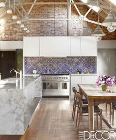 This barn renovated kitchen in Suffolk, England is full of pattern with exposed red brick walls, blue and white tile backsplash, marble center island, exposed gable ceiling and warm wood dining table.