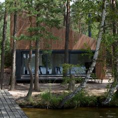 This wedge-shaped cabin in the Czech Republic has a folding screen set into one of its slatted timber facades to open the interior out to a nearby lake.