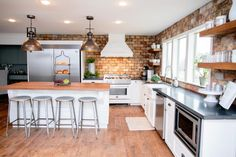Features in the new kitchen include open shelving, farm sink, industrial style pendant lights and honed granite countertops that contrast smartly with the white cabinets.