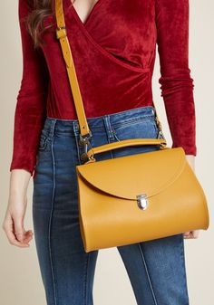 "The Cambridge Satchel Company Poppy Bag in Mustard - 11"" - Sleek English design with a retro, feminine twist - that's what this Poppy bag from The Cambridge Satchel Company promises, and it certainly delivers! Crafted from soft, textured leather in a gorgeous mustard hue, safely fastened with a gleaming push lock closure, and finessed with an optional strap, this classic purse lends its heritage-driven aesthetic to your every ensemble."