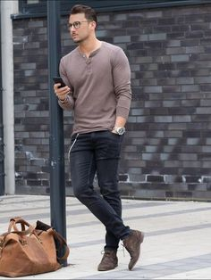 Coole Kombination aus Blackdenim-Jeans und taupefarbenem Henleyshirt und passenden Desertboots.