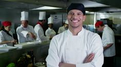 Portrait of a happy young trainee chef or worker in a commercial kitchen. The rest of the team of staff are working together, preparing food in the background. In slow motion. - HD stock video clip
