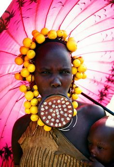 Mursi woman with pink parasol, Mago, Ethiopia by Cezary Filew.