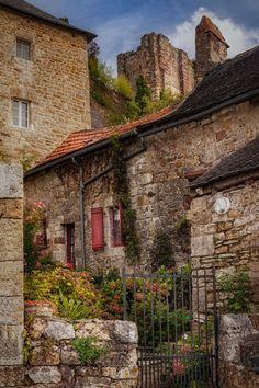 Turenne - Une autre magnifique résidence fleurie de Turenne et le château-fort en arrière plan. Le village, perché sur une butte du Jurassique, se situe aux confins de la Corrèze (région Limousin) au nord, à 3 km du Lot (région Midi-Pyrénées) au sud, et à quelques kilomètres du Périgord (région Aquitaine) à l'ouest.