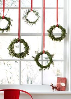 No matter your holiday decorating style, everybody loves a good evergreen wreath. Pick up these small styles at a Christmas tree stand or the craft store to stagger across your bare windowpanes for a visual treat that you and your neighbors can enjoy.