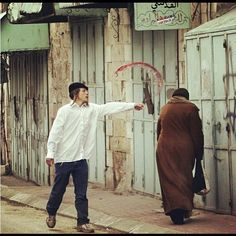 """ISRAELI ZIONIST SETTLER TAUNTING AN ISRAELI ARAB. THEY WANT ALL ARABS AND CHRISTIANS OFF THE LAND AS """"THEY ARE THE CHOSEN PEOPLE"""". SUCH A DIRTY GAME"""