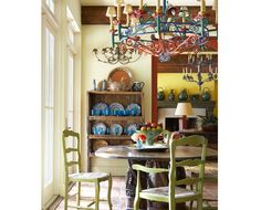 Colorful vintage chandelier from Mexico with turquoise Mexican glassware from the 20s displayed in trastero