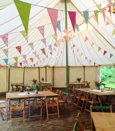 The natural canvas marquee at The Keeper and the Dell in Norfolk, complete with rustic wooden table and chairs, pretty enamel jugs with flowers, vintage bunting, festoon lighting and chandeliers ~ perfect for a country outdoor wedding