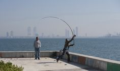 throw it further ! - man flyfishing whilst his friend is watching the action on a sunny autumn day on the waterfront in karsiyaka,izmir,turkey.new scyscrapers under construction can be seen at the background.