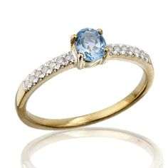 Anillo ORQUIDEA- Topacio azul Sortija de oro amarillo de 9 kts. montado con topacio azul en garra central, acompañado de diamantes laterales en talla brillante.