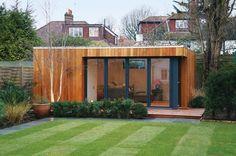 chalet de jardin habitable de design contemporain aménagé avec un mobilier gris et une baie coulissante vitrée