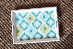 """Re-do breakfast tray: """"The whole process was super simple, I just gave the tray a couple of coats of spray paint, cut the fabric to size and used some spray adhesive to adhere it to the bottom of the tray. Then, I used a small craft brush to dab the edges of the fabric with some Mod Podge, just to make sure it doesn't fray and is really suck down."""""""