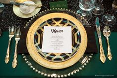 photo of a wedding dinner table at the Ohio Statehouse, modern design with dark green table linens, black sequined table runner, gold flatware and black and gold place settings, emerald and gold color palette.  Menu, place cards and calligraphy by On Paper.