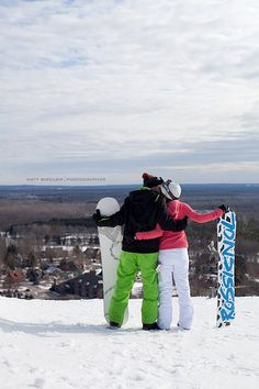 Sharing a kiss with a view on their snowboarding engagement session!