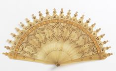 Brisé fan of blond horn decorated with gilt painting and steel piqués. c1820. English? Cooper Hewitt.
