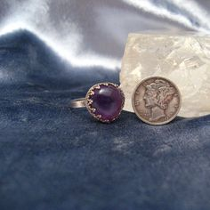 This bold ring has been created using silver and a natural amethyst cabochon in a custom, filigree basket bezel. The gorgeous, dark purple amethyst is heart shaped and domed. The ring sits up a tad under 1/2 inch off the finger. The ring will fit a size 6.75....just a tad under size 7.  The top measures .55 mm or a tad over 1/2 inch in diameter.  Weight: 4 Grams  The ring is in best vintage condition. There are no chips to the stone. The metal tests as sterling besides being marked ...