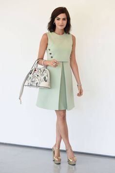 Camilla Belle pairs a mod-inspired Gucci dress with a flora handbag for a classic look. Click here for more style tips.
