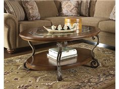 """Shop for Signature Design by Ashley Oval Cocktail Table, T517-0, and other Living Room Tables at Hickory Furniture Mart in Hickory, NC. With the scrolling bronze color finished metal adorned with wirework detail supporting warm burnished finish table tops, the """"Nestor"""" accent table collection beautifully captures the elegance and grandeur of fine traditional design."""