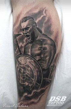 Black and grey style Ragnar Lodbrok holding a Real Madrid shield tattoo on the left leg.