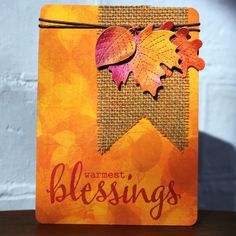 handmade Autumn card from Ideas & Paper ... luv the gorgeous impressionistic background paper in oranges ... big script sentiment stamped directly on the card ... burlap fishtail pennant ... die cut leaves painting with shimmery watercolors ... luv it!