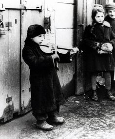 Joe Heydecker A child playing a violin in a ghetto street Warsaw, Poland, February 1941 [From the Réunion des Musées Nationaux] Jewish History, World History, Warsaw Ghetto, Warsaw Poland, Poland Ww2, Boys Playing, Second World, World War Two, Historical Photos