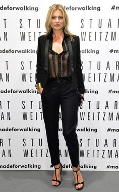 Kate Moss rocks all black in a Saint Laurent jacket and sheer blouse with black trousers at the Stuart Weitzman Flagship Store Opening in Milan.