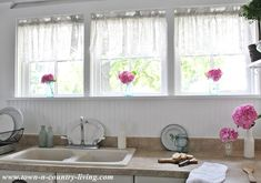 Farmhouse Kitchen Windows get prettied up with pink hydrangeas tucked in blue Ball Mason jars.