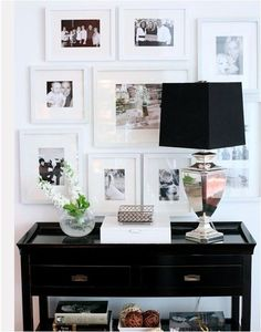 black and whites over entry table.  White frames keep it from being too busy, black lamp shade is great.  Nice change of pace from one big mirror or picture.