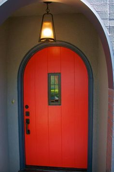 A rounded, wood-paneled door creates a cozy cottage entry. A small window insert helps to break up the bright red color while still providing a bold curb appeal design.