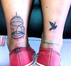 A bird cage and a bird on both ankles of a woman. Color: Black. Tags: Matching