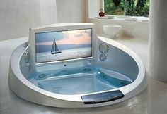 Circular shaped tub with a built in entertainment set up. If you want to take your time soaking in the tub while watching your favorite game then this is a great design to work with.