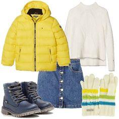 Piumino giallo e maglione bianco con collo alto e bordo in contrasto, tutto griffato Tommy Hilfiger. Gonna in jeans con elastico in vita e bottoni sul davanti. Stivaletti stringati in fintapelle e guanti con righe colorate.